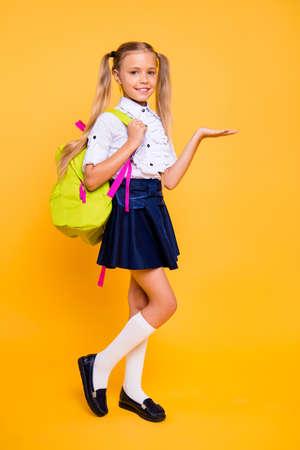Longitud total, piernas, cuerpo, tamaño de perfil vertical Foto de vista lateral de una niña pequeña hermosa, adorable y guapa aislada sobre fondo amarillo que sostiene un producto invisible en la palma de la mano