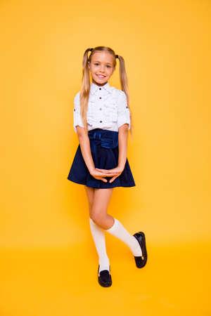 Volledige lengte, benen, lichaam, grootte verticaal portret van prachtige, knappe kleine blonde meisjestribune die op glanzend gele achtergrond wordt geïsoleerd
