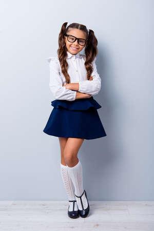 Longitud total del tamaño del cuerpo de una niña bonita, linda, adorable, adorable, encantadora y elegante con coletas rizadas en una blusa blanca formal, una falda azul corta. Aislado sobre fondo gris