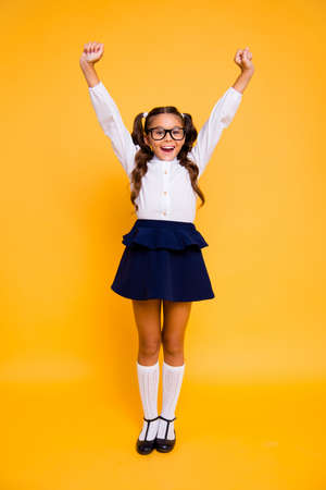 1-september and back to school concept. Full length, legs, body, size vertical portrait of crazy small girl in skirt stand isolated on vivid yellow background raising her fists, hands up