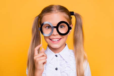Im so educated! Close up studio photo portrait of pretty adorable nice cheerful glad lovely little girl teen with toothy beaming smile making false glasses isolated bright background