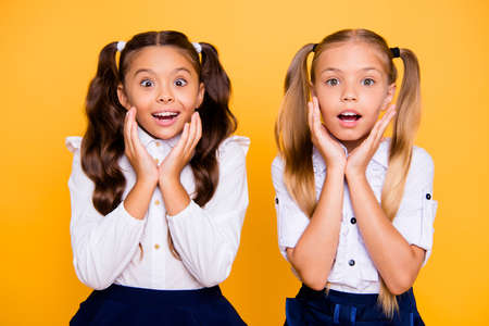 Close up portrait of cute, nice, lovely, sweet surprised small girls hold hands near the face isolated on yellow background