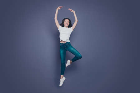 Graceful adorable pretty stylish trendy nice lovely cheerful curly-haired brunette girl in casual white t-shirt and jeans, fooling, flying in air, dancing like ballet, isolated on grey background Imagens