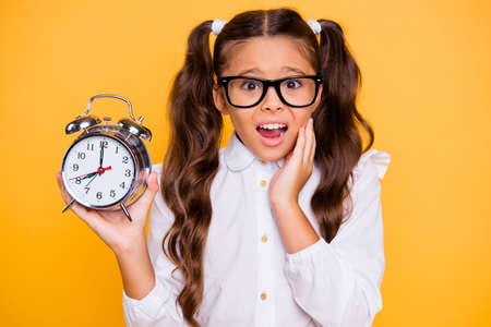 1-september concept. Close up portrait of scared and confused small brunette girl with watch in hands isolated on shine yellow background