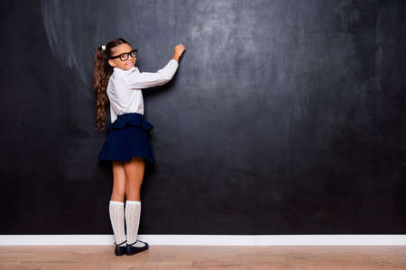 Full size body length of nice genius adorable lovely small little girl with curly pigtails in white formal blouse shirt, blue skirt, writing on blackboard. Isolated over black background Foto de archivo