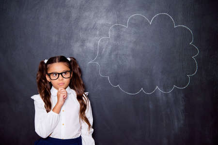 Portrait of nice cute genius pensive adorable lovely small little girl with curly pigtails in white formal blouse shirt, blue skirt, thinking. Isolated over black background