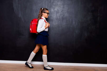 Full size body length profile side view of nice smart cute stylish small girl with curly pigtails in white blouse shirt and blue skirt with red bag, going to school. Isolated over black background Banque d'images - 107152008