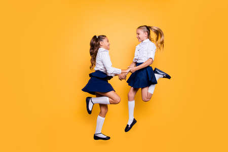 Back to school concept. Full length, legs, body, size profile side view portrait of carefree, careless, small girls in skirts jumping isolated on yellow background hold hands looking at each other
