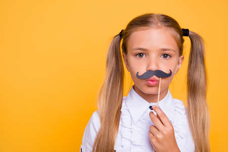 Time for fun concept! Close up portrait of joyful, craz small blonde girl with fake mustache isolated on yellow background with copy space for text