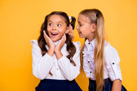 Close-up portret van klein blond meisje geïsoleerd op levendige gele achtergrond gebogen om het interessante nieuws of geheim van brunette vriend met wow gezicht te vertellen Stockfoto