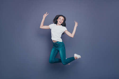 Adorable pretty lovely stylish nice cheerful dreamy curly-haired brunette girl in casual white t-shirt and jeans, flying in air, showing double v-sign, isolated on grey background Stock Photo