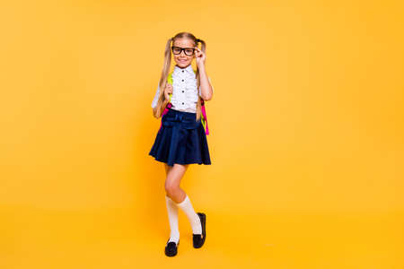Full length, legs, body, size portrait of beautiful, charming, gorgeous small blonde girl in skirt stand isolated on shine yellow background with copy space for text corrects glasses Фото со стока