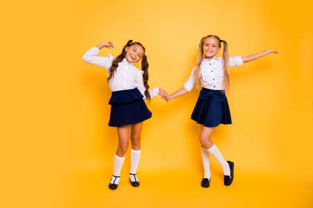 Back to school concept. Full length, legs, body, size portrait of small girls happily jump holding hands isolated on bright yellow background