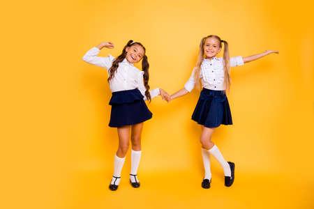 Zurück zum Schulkonzept. In voller Länge, Beine, Körper, Größenporträt von kleinen Mädchen springen glücklich Händchenhalten isoliert auf hellgelbem Hintergrund