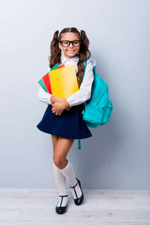 Full size body length of cute cheerful lovely stylish adorable small little girl with curly ponytails in blouse shirt and blue skirt, keeping color book pile, folders. Isolated over grey background