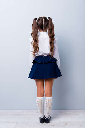 Snap shot rear back view of nice adorable stylish girl with curly pigtails in formal white blouse shirt, short blue skirt, gaiters, shoes. Isolated over grey background