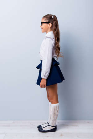 Snap shot profile side view of nice cute cheerful adorable lovely stylish small girl with curly ponytails in white formal blouse shirt, short blue skirt, gaiters. Isolated over grey background