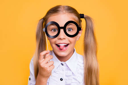 I do not want to go to school! Close up photo portrait of sweet funky small nice girl holding black big glasses on stick in hand tongue out looking at camera isolated bright color vivid background Stock Photo