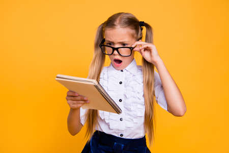What is it! I do not understand it! Close up photo portrait of sad angry annoyed upset schoolkid with open mouth adjusting glasses staring looking at copybook textbook isolated bright background Standard-Bild