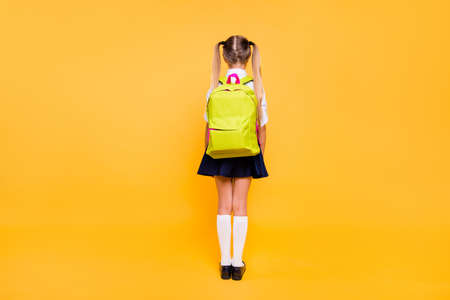 Full length, legs, body, size back behind rear view photo of girl in blue skirt with yellow lemon rucksack small girl isolated on bright yellow background with copy space for text 스톡 콘텐츠