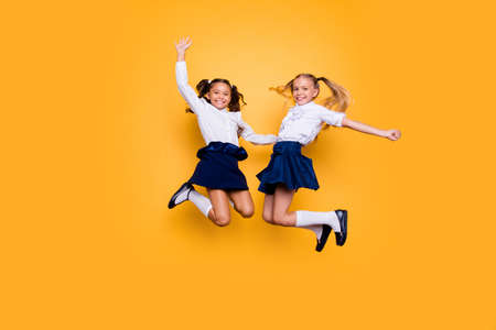Achievements concept, dynamic images. Full length, legs, body, size portrait of carefree, careless, small girls jumping isolated on yellow background raised fists up Banque d'images - 107152043