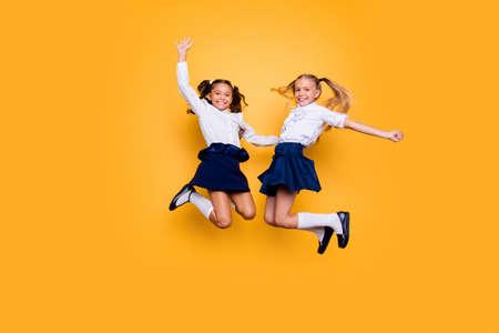 Leistungskonzept, dynamische Bilder. Volle Länge, Beine, Körper, Größenporträt von sorglosen, sorglosen, kleinen Mädchen, die isoliert auf gelbem Hintergrund springen, erhoben Fäuste