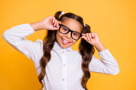 Portrait of cheerful, cute, fun, play, funky, joyful, crazy small girl isolated on vivid yellow background look at camera and show tongue out