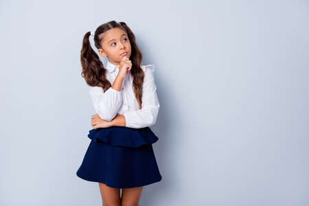 Nice cute dreamy adorable lovely stylish girl with curly pigtails in white blouse shirt and dark blue shirt skirt, thoughtful gesture, hand fist to chin, copy-space. Isolated over grey background