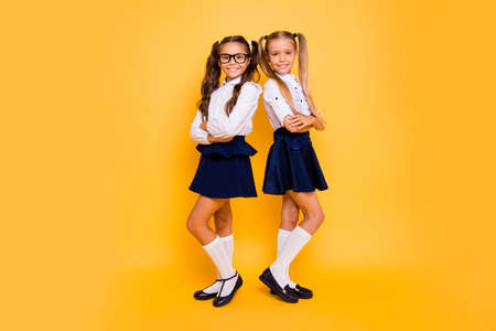 Full length, legs, body, size portrait of gorgeous, adorable, good-looking small girls stand back-to-back with crossed arms isolated on shine yellow background
