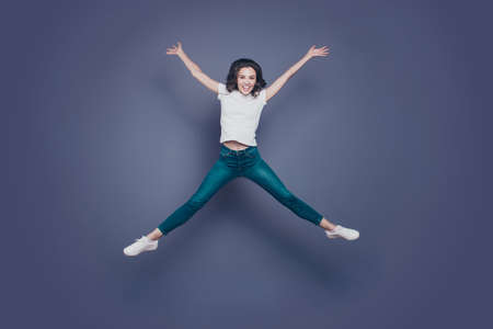 Crazy attractive pretty stylish trendy nice lovely cheerful curly-haired brunette girl in casual white t-shirt and jeans, flying up in air like star figure, isolated on grey background Фото со стока