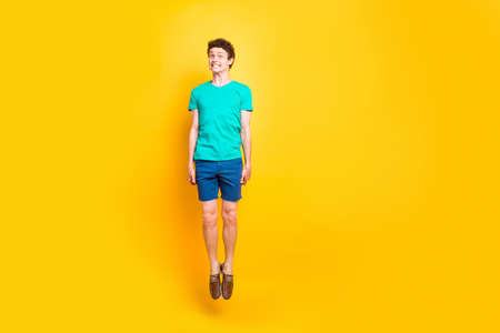 Full size length body picture of handsome curly-haired playful young guy wearing casual green t-shirt, shorts, shoes, jumping up in air, grimacing. Isolated over yellow background Stock Photo