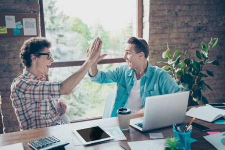 Successful online business project. Two cheerful glad satisfied delighted guys, friends sitting in front of laptop, clapping palms light interior room, entrepreneurs, meeting, gathering Banco de Imagens