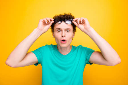 Handsome curly-haired shocked young guy wearing casual green t-shirt, showing surprised gesture, putting glasses up. Isolated over yellow background Foto de archivo - 107216674