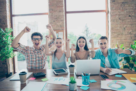 Four cheerful glad satisfied people, friends, guys and girls celebrating successful project completing at industrial interior room, meeting, gathering Stock Photo