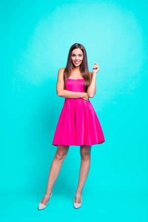 Full length size body vertical picture of young straight-haired nice tender brunette smiling girl, wearing pink mini short dress. Isolated over bright vivid teal turquoise background