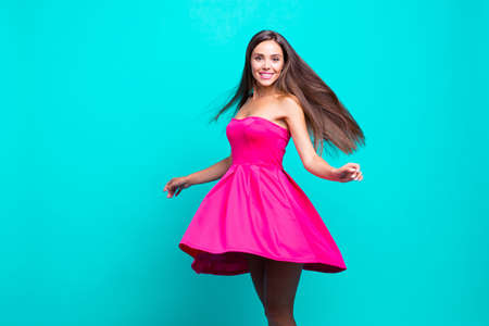Young straight-haired sweet brunette smiling girl wearing pink dress, dancing, flirting, wind blows skirt and hair. Copy space. Isolated over bright vivid turquoise background