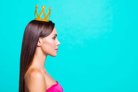 Half faced turned close up studio photo portrait of pretty attractive confident charming cute lovely serious lady wearing crown on head isolated on bright vivid blue background Stock Photo