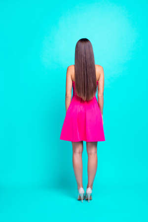 Rear back full body vertical view of straight-haired sweet tender brunette young girl with long hair, wearing pink mini short dress, standing. Isolated over bright vivid turquoise background