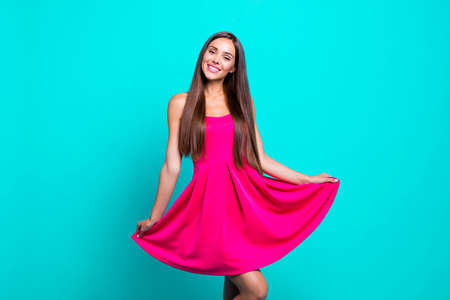 Young straight-haired sweet brunette smiling girl wearing pink dress, dancing, flirting. Copy space. Isolated over bright vivid turquoise background Фото со стока