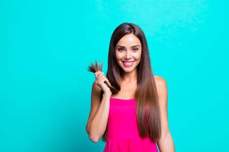 Schließen Sie herauf Fotoporträt der frohen netten hübschen zufriedenen Dame, die in der Hand hält, die gesunde Enden lokalisiert auf hellblauem Hintergrund zeigt Standard-Bild