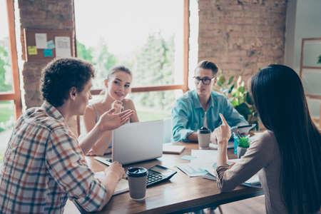 Entreprise de jeunes et gais gars assis à une table en bois discutant et projet de geste sur le lieu de travail Banque d'images