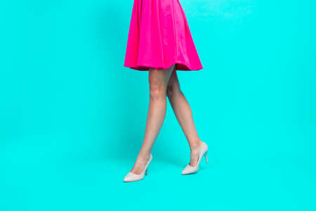 Close-up picture of young girl legs, pink fuchsia short mini dress, making steps in high heels shoes. Copy space. Isolated over bright vivid turquoise teal background Stock Photo
