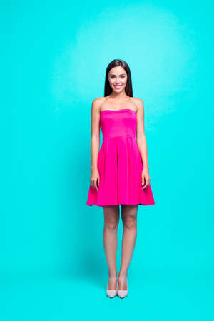 Full body length size vertical of smiling brunette girl, lady in mini pink dress and high heels shoes, standing straight. Isolated over bright vivid turquoise background