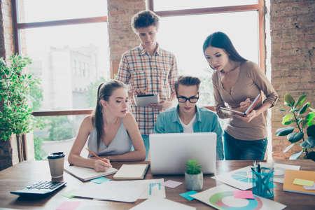 Concept van gezamenlijk werk op kantoor. De leerlingen kijken naar de monitor en proberen de voorwaarden van de taak te begrijpen en schrijven de oplossing op in notitieboekjes Stockfoto