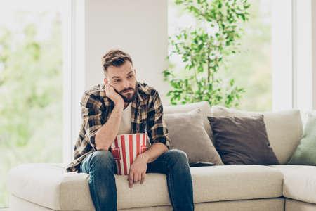 Barbuto brunet uomo stanco in camicia a scacchi e jeans denim look