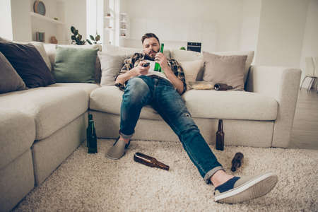 Brunet drunk man lies on a white couch at home in blue jeans and 免版税图像