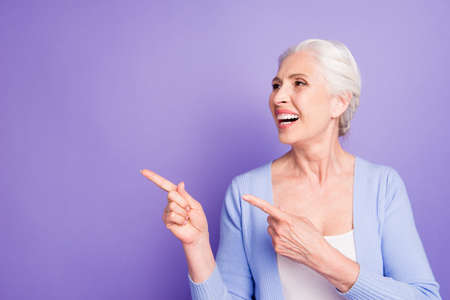 Grey haired old nice beautiful smiling woman pointing with two f Stock Photo