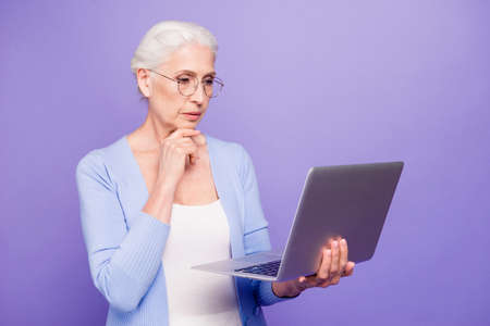 Gray haired old serious minded business woman wearing glasses, h Stock Photo