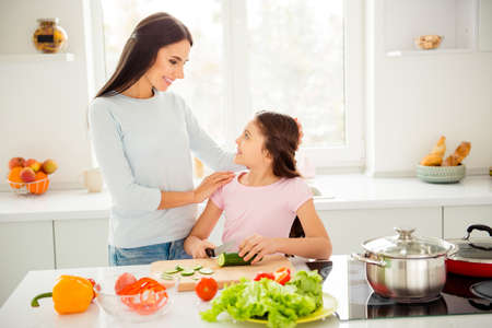 Beautiful charming mom and her small little daughter cooking gre Stock Photo