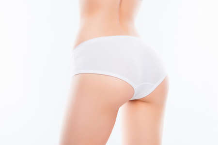 Close up photo of fit womans ass with perfect ideal skin in white